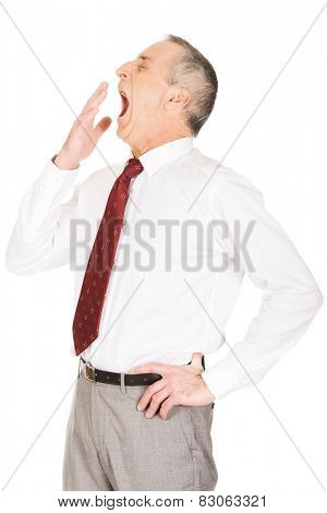 Exhausted sleepy mature businessman yawning.