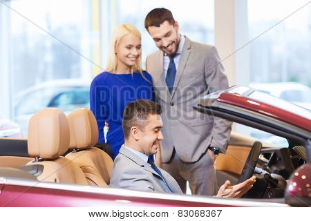 auto business, car sale, consumerism and people concept - happy couple with car dealer in auto show or salon