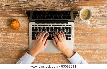 business, education, people and technology concept - close up of female hands with laptop computer, muffin and coffee cup on table