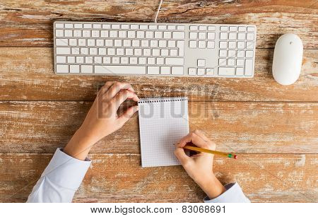 business, education, technology and people concept - close up of female hands with notebook, pencil and computer keyboard on table
