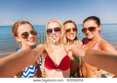summer vacation, holidays, travel and people concept - group of young smiling women photographing by camera or smartphone on beach