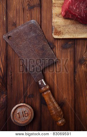 meat cleaver butcher knife with raw beef meat fillet  on wooden  table  and 1lb iron weight