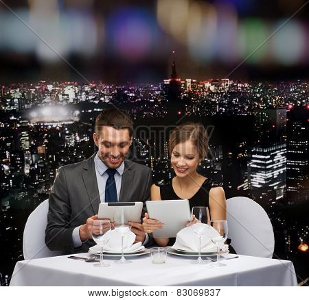 restaurant, couple, technology and holiday concept - smiling couple with menus on tablet pc computers at restaurant