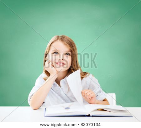 education, people, children and school concept - little student girl sitting at table with book over green chalk board background