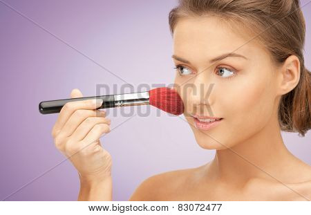 people, beauty, makeup and accessories concept - close up of young happy woman applying blush with brush over violet background
