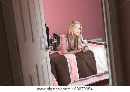 Teenage girl use cellphone in her room.