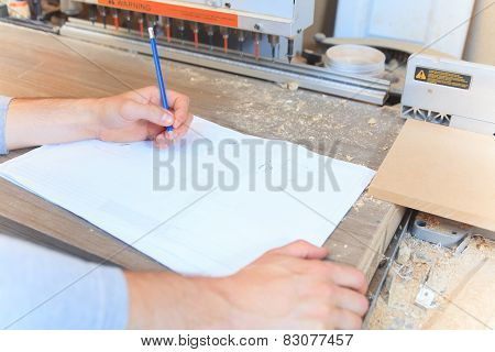 An adult carpenter measuring wood with ruler at table in workshop