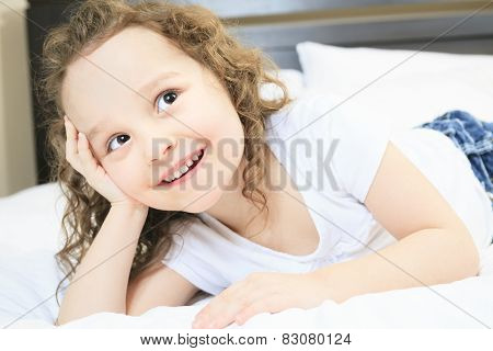 A portrait of a little girl on bed
