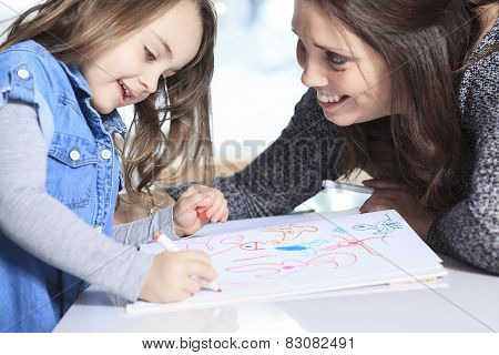 A mother and daughter drawing in a book on the kitchen
