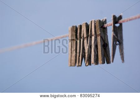 Close-up of frozen old wooden clothespins hanging on wire in row
