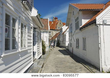 Tourist walks by the street of the old town in Stavanger, Norway.