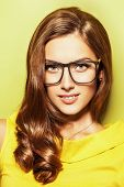 foto of spectacles  - Beauty portrait of a positive young woman in spectacles and bright yellow dress over green background - JPG
