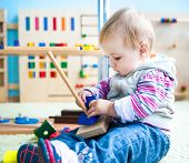 pic of playgroup  - little girl in the classroom early development plays with numerous bright toys - JPG