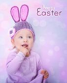 stock photo of bunny costume  - Portrait of happy adorable child wearing cute knitted hat with rabbit ears on pink blur background - JPG