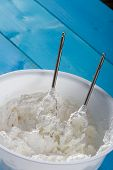 stock photo of whipping  - Natural light photo of whipped Cream and whisk in Plastic Bowl - JPG