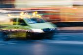 stock photo of ambulance car  - Ambulance Car in a Blurred City Scene - JPG