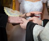 picture of priest  - Priest changes rings on his fingers the married couple bride and groom