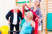 stock photo of physical exercise  - Seniors in physical rehabilitation therapy with trainer - JPG