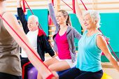 pic of gym workout  - Senior people at fitness course in gym exercising with stretch band - JPG