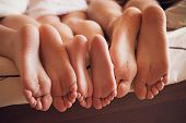 image of legs feet  - close up of a family showing off their feet under the covers - JPG