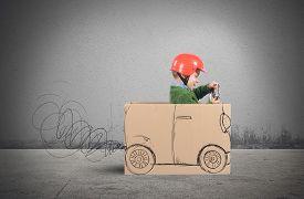 foto of creativity  - Creative baby plays with his cardboard car - JPG