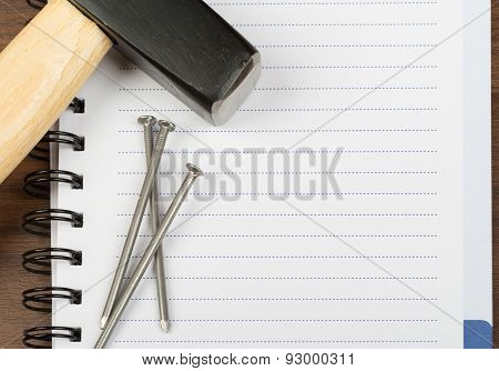 Hammer with nails on blank note pad