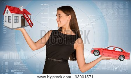 Smiling businesslady holding car and house