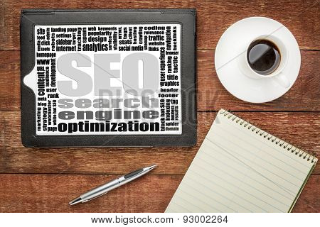 search engine optimization (SEO) word cloud on a digital tablet with coffee and notepad