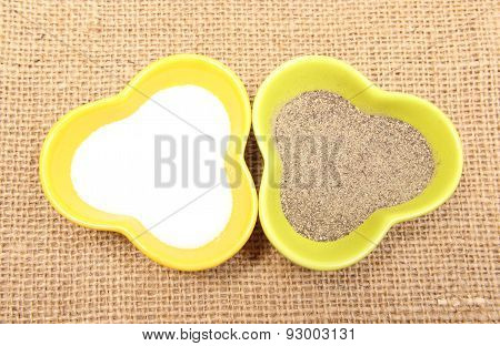 Powdery Pepper And Salt In Colorful Bowl On Jute Canvas