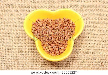 Buckwheat Groats In Yellow Bowl On Jute Canvas
