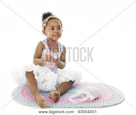 An adorable 2 year old sitting pretty barefoot in her petticoat and adorned with beads.  She sits on a pastel rag rug.  On a white background with space on the right for your text.