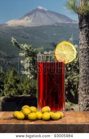 Glass Of Vermouth With Olives On A Wood Table