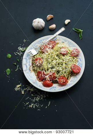 Pasta spaghetti with pesto sauce, basil, garlic, baked cherry-tomatoes on rustic dark table, top vie
