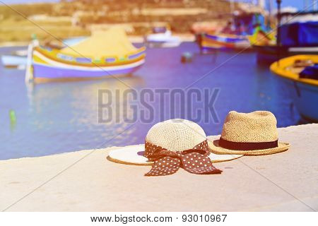 two hats with traditional maltese boats on background