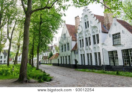 Bruges, Belgium - May 11, 2015: People Visit White Houses In The Beguinage (begijnhof) In Bruges