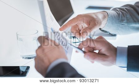 Businessmen Examining A Financial Report