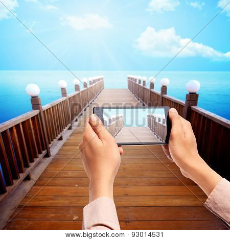 Man Hand Take Picture Of Wooden Pier Using Cellphone