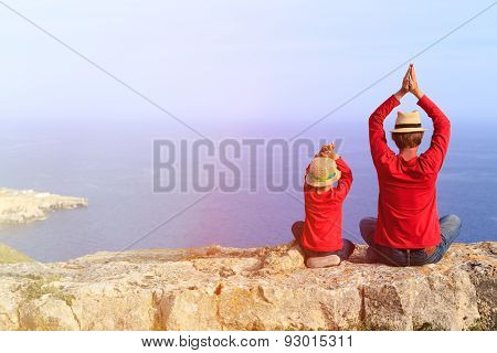 father and son doing yoga in mountains at the sea