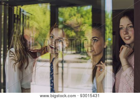 Women At The Window Looking At Something Through The Glass