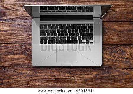 Open laptop on brown wooden table. Top view
