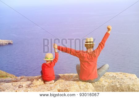 happy father and son sitting on top of a mountain