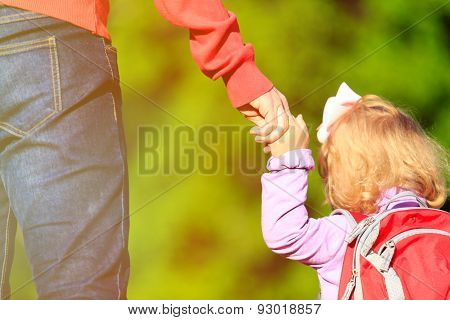 Mother holding hand of little daughter outdoors