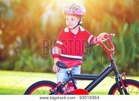 Little boy with bicycle standing outdoor on sunny day, child having fun playing sports in the park, activities for kids in summer camp