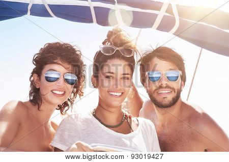 Portrait of happy three people having fun on sailboat, best friends traveling together, enjoying bright sunny summer days in sea cruise