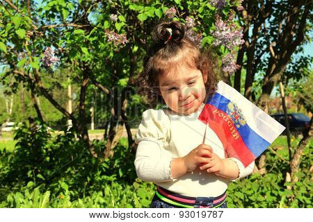 Small Girl Stands With Flag Of Russia In Front Of Lilac Bush On Sunny Day