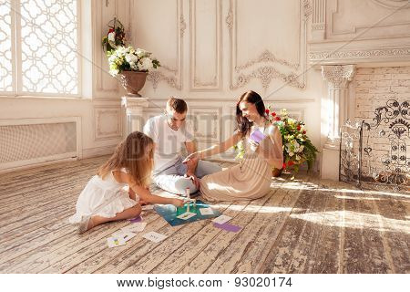 Beautiful family playing  funny boad game on floor