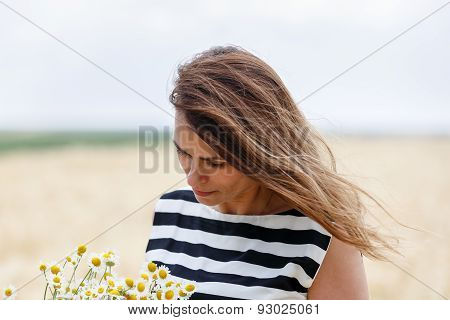 Beautiful Woman Smelling Flowers In Nature