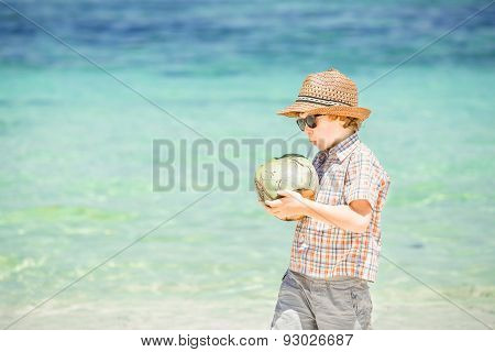 Happy young boy staying on beautiful ocean beach wearing hat and sunglasses holding coconut in his h