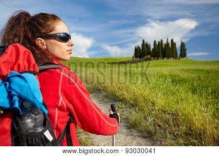 Female hiking woman happy and smiling during hike trek on Toscana hills