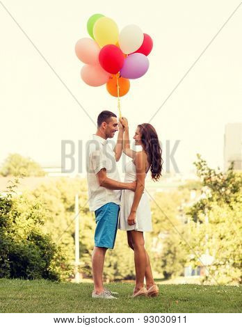 love, wedding, summer, dating and people concept - smiling couple wearing sunglasses with balloons hugging in park